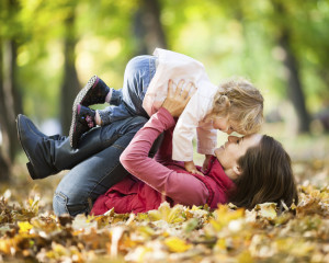 Happy family playing against blurred autumn leaves background