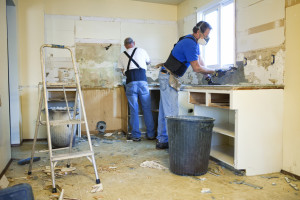 Two men tearing out old kitchen during home renovations.